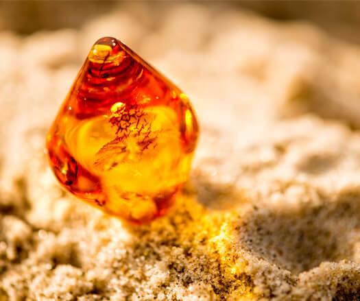 Pedra de âmbar colocada sobre a areia em um case de criação de site e identidade visual