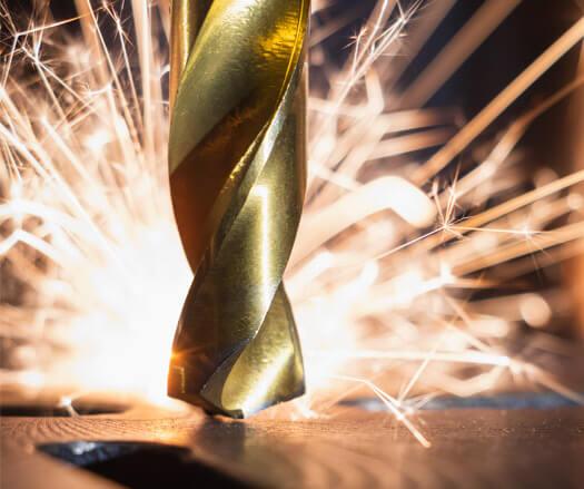 Broca perfurando metal com faíscas sendo lançadas. Criação de sites da Calfér
